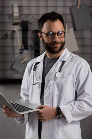 smiling male doctor in white coat with stethoscope over his neck holding laptop in hands
