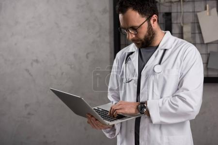 Photo for Doctot in white coat with stethoscope over his neck using laptop - Royalty Free Image