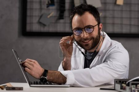 smiling doctor in white coat and stethoscope using laptop while  looking at camera