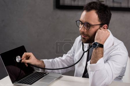 Photo for Repairman in doctor white coat using stethoscope to diagnose laptop - Royalty Free Image