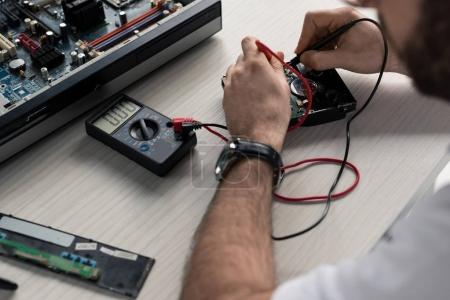 cropped image of man using multimeter with testing hard disk drive