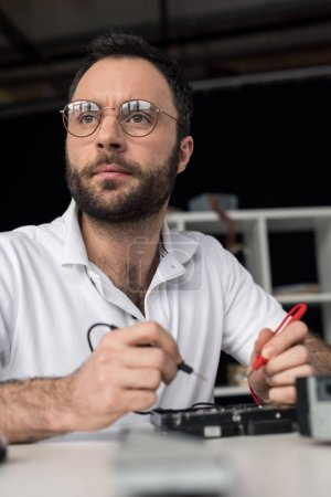 Foto de Reparador con multímetro mientras prueba unidad de disco duro y mirando lejos - Imagen libre de derechos
