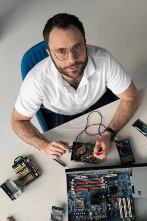 man using multimeter while testing hard disk drive