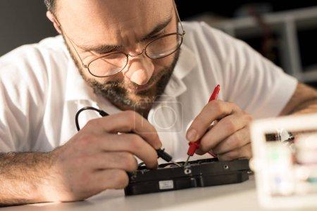 Photo pour Homme à l'aide du multimètre pendant le test d'unité de disque dure - image libre de droit