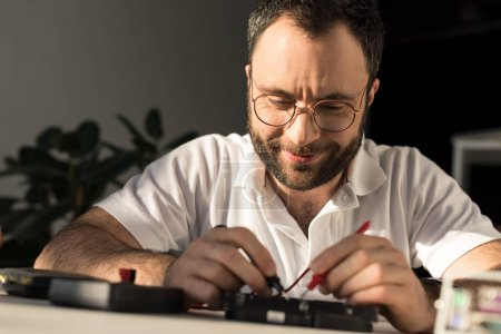 Photo for Smiling man using multimeter while fixing pc - Royalty Free Image