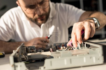 man using tongs while fixing broken pc
