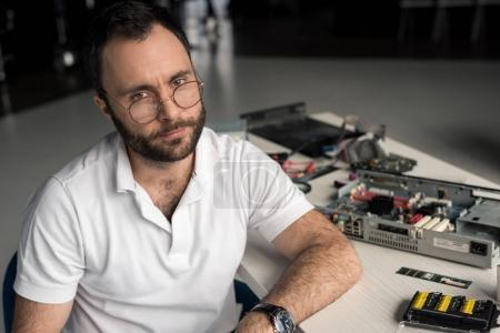 man with hand on table looking at camera