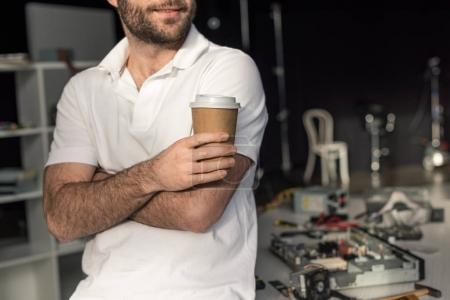 cropped image of man holding cup of coffee