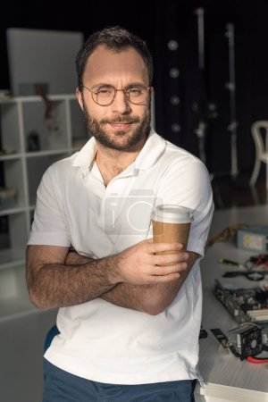 man with coffee in hand looking at camera while leaning on table