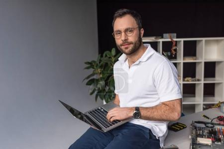 man sitting on table and using laptop