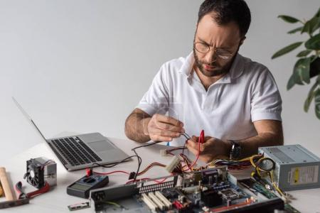 man using multimeter while fixing broken computer and looking down