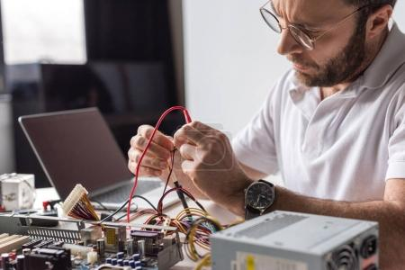 Photo for Man using multimeter while fixing broken computer - Royalty Free Image