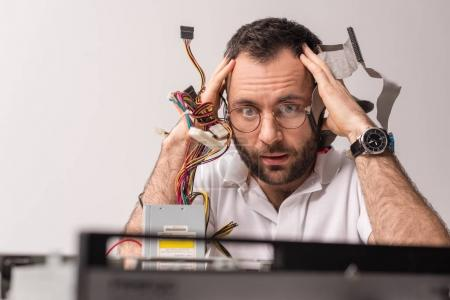 scared man with wires in hands near his head looking on broken pc