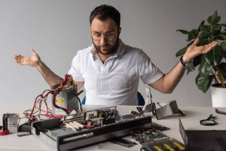 bewildered man with arms outstretched looking on broken pc