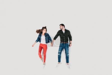 Photo pour Vue de dessus de couple heureux élégant tenant les mains isolées sur blanc - image libre de droit