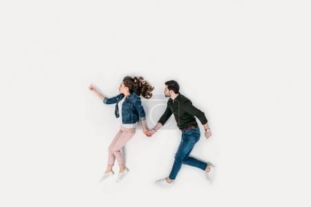 top view of couple walking and holding hands isolated on white
