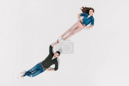 top view of stylish man carrying his girlfriend with one hand isolated on white