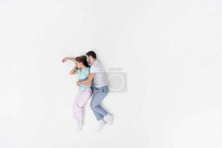 top view of couple in pajamas embracing and sleeping together isolated on white