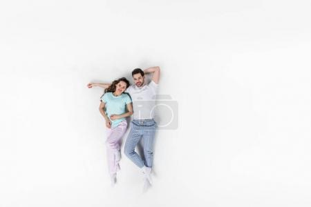 top view of couple in pajamas lying together isolated on white