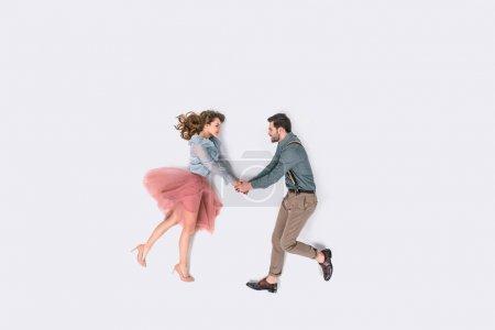 Photo pour Vue de dessus de élégant jeune couple tenant les mains isolées sur blanc - image libre de droit