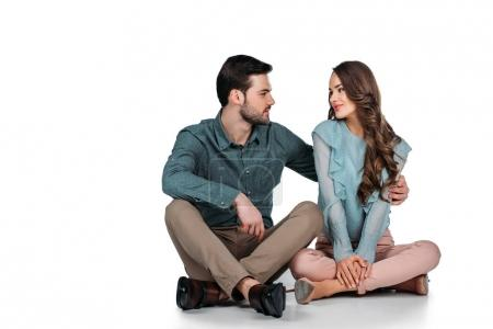 attractive young couple sitting on floor on white