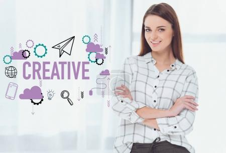 attractive businesswoman standing with crossed arms and looking at camera, creative icons