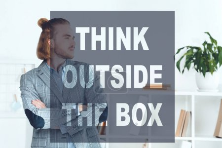 handsome businessman standing in office with crossed arms and looking away, think outside the box concept