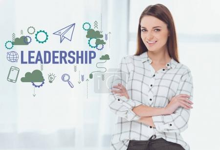 attractive businesswoman standing with crossed arms and looking at camera, leadership concept