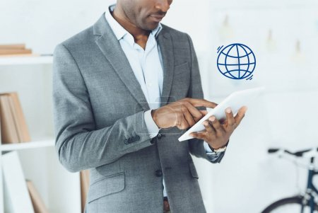 cropped image of african american man using digital tablet and globe symbol