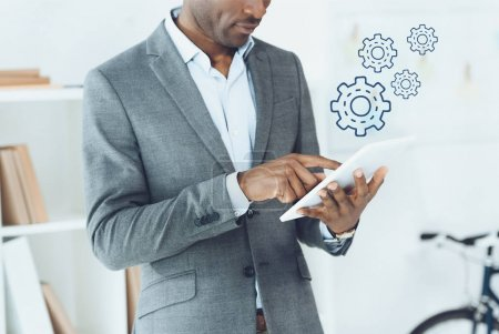 cropped image of african american man using digital tablet and cogwheels icons