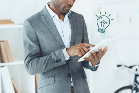 Photo for Cropped image of african american man using digital tablet with light bulb symbol - Royalty Free Image