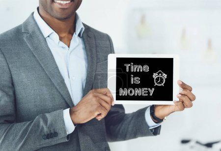 cropped image of smiling african american man showing digital tablet with inscription time is money