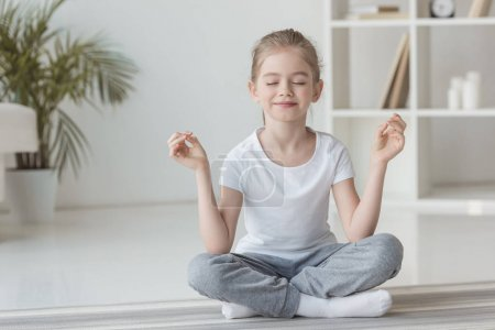 smiling little child meditating in lotus pose at home