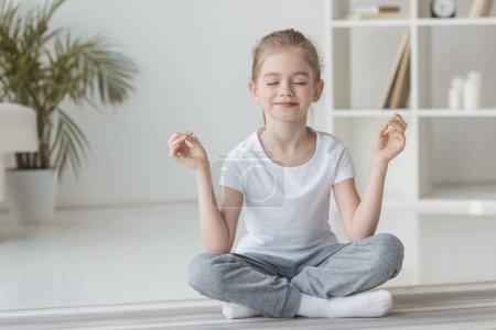 Photo pour Fillette souriante méditation en posture de lotus à la maison - image libre de droit