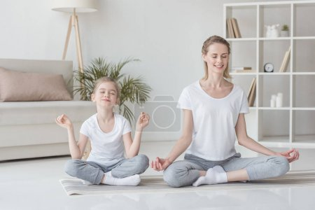 mother and daughter sitting in lotus pose at home and meditating together