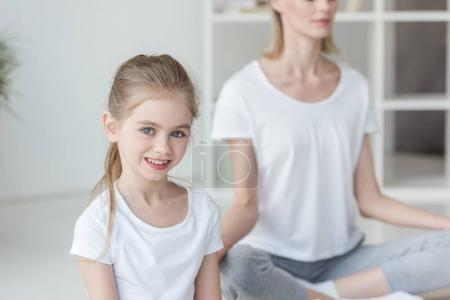 happy little child practicing yoga with mother