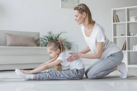 mother helping her daughter to do forward bend at home