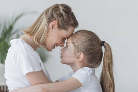 Photo for Close-up portrait of mother and daughter embracing and cuddling - Royalty Free Image