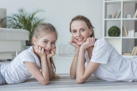 happy mother and daughter lying on floor together and looking at camera