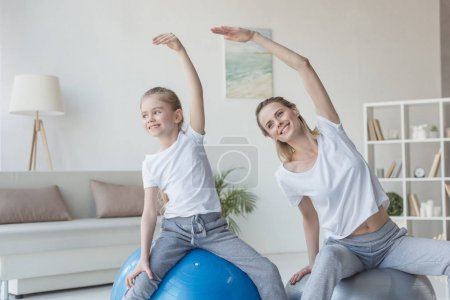 mother and daughter doing side bends on fit balls