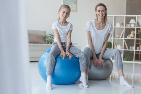 smiling mother and daughter sitting on fit balls at home