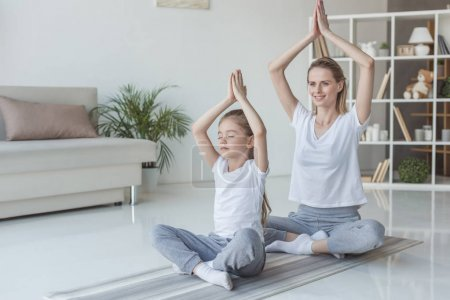 mother and daughter practicing yoga in lotus pose at home
