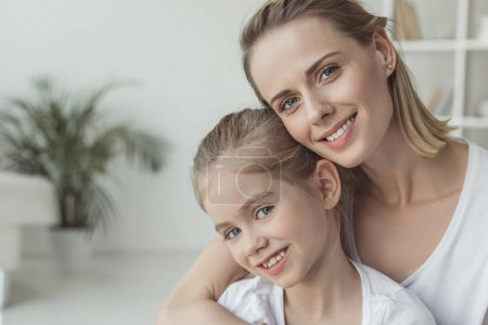 close-up portrait of mother and daughter embracing at home