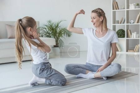 mother showing biceps muscle to her daughter at home