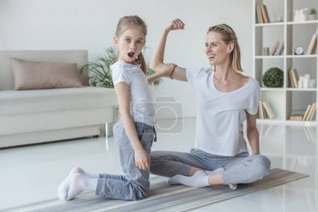 mother showing biceps muscle to her shocked daughter at home