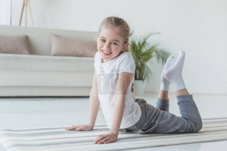 happy little child doing backbend on yoga mat and looking at camera