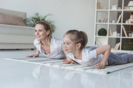 Photo pour Mère et la fille faisant push ups ensemble sur le tapis d'yoga à la maison - image libre de droit