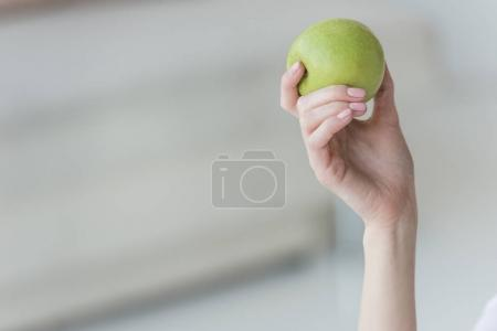 cropped shot of woman holding fresh green apple