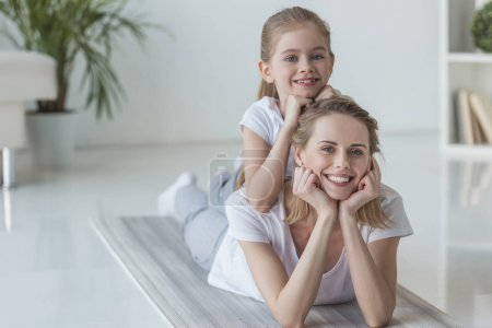 happy mother and daughter lying on floor together