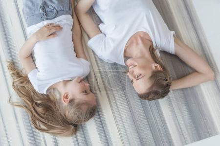 top view of mother and daughter lying on floor